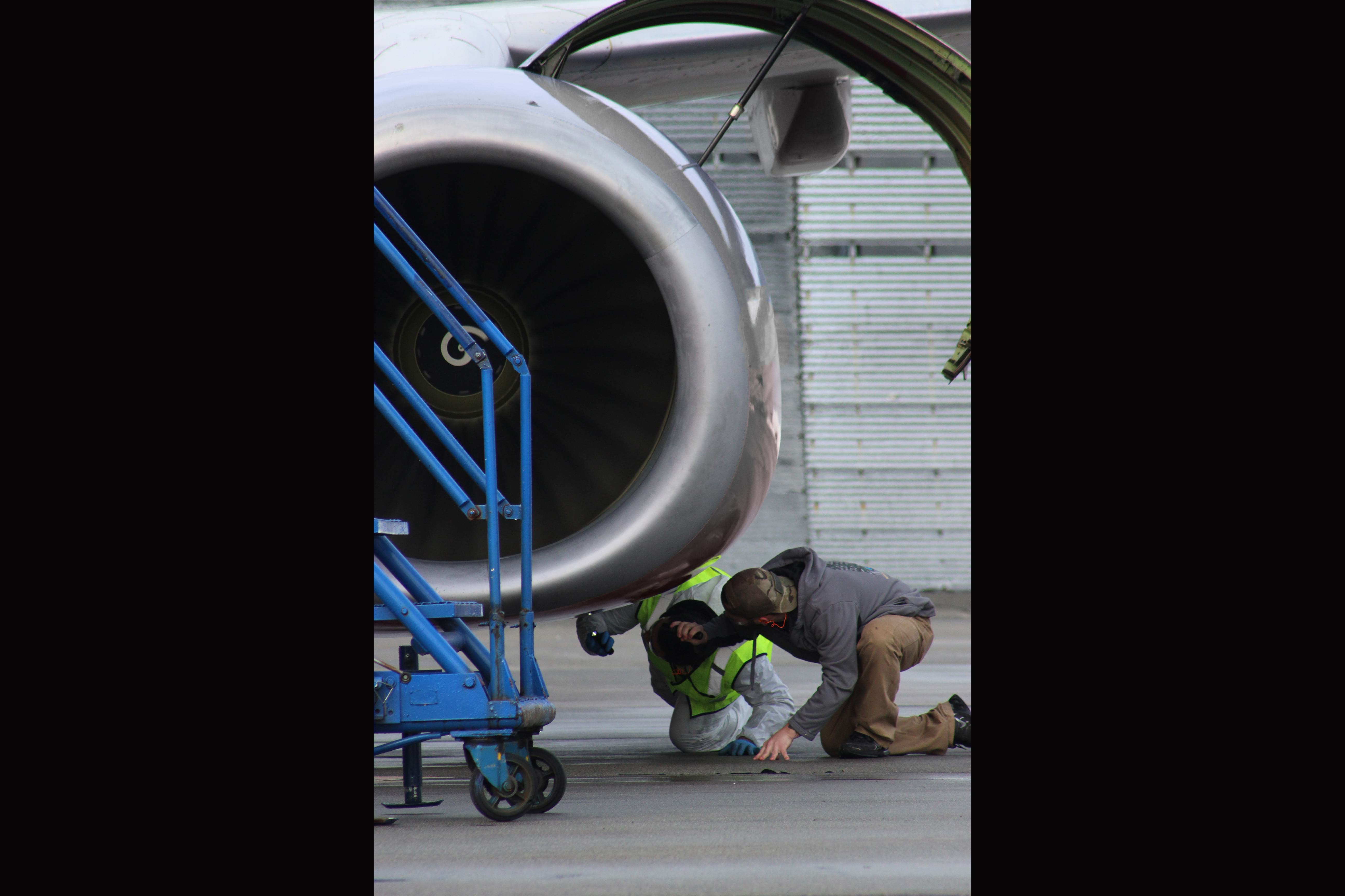 An Apprentice Mechanic (left) performs a post-engine run inspection under the guidance of a senior mechanic.
